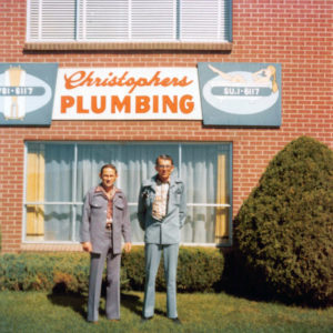 Christopher's Plumbing sign on building with 2 men standing out front